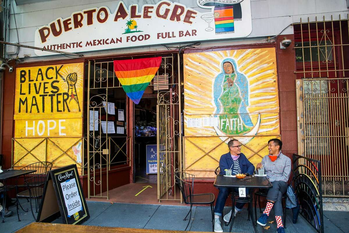 David Hemminger, left, and Eric Pascual, right, enjoy some margaritas and chips on the sidewalk at Puerto Alegre on July 15, 2020. They live in the Mission and enjoy eating out on the sidewalk, only a few monutes walk from home.