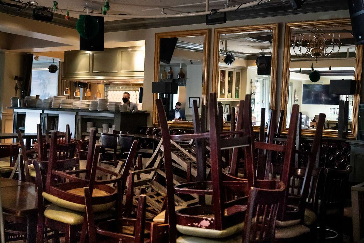 Chef Jorge Carmona works in the kitchen behind stored chairs in the restaurant of Rosie McCann's at Santana Row on Wednesday, July 15, 2020 in San Jose, Calif. They are not allowed to have indoor dining.