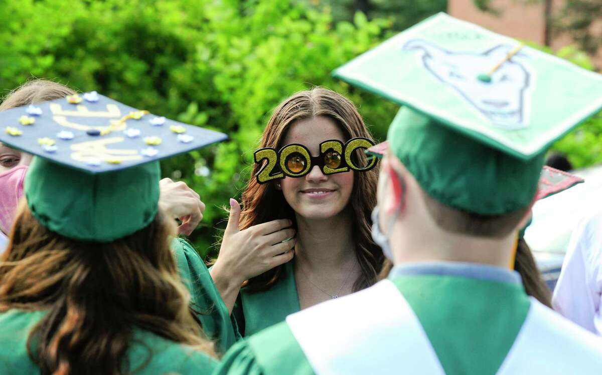 Mackenzie Kuehn, center, gives a thumbs up as she chats with fellow graduates prior to Trinity Catholic High School's final graduation ceremony on July 16, 2020 in Stamford, Connecticut. Trinity Catholic opened its doors in 1958 as Stamford Catholic High School and the first graduating class was in 1960. The Class of 2020 is comprised of 84 graduates, representing Stamford and its surrounding towns, as well as international students from China.