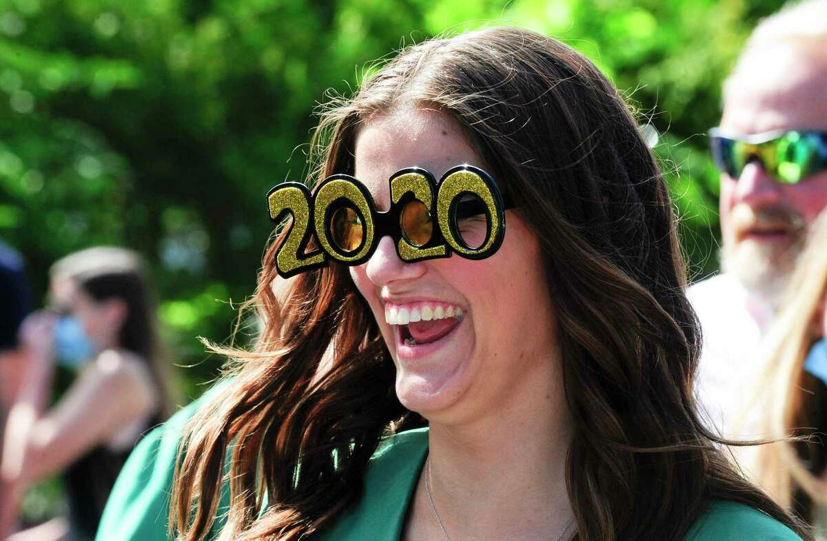 Mackenzie Kuehn sports 2020 glasses up as she chats with fellow graduates prior to Trinity Catholic High School's final graduation ceremony on July 16, 2020 in Stamford, Connecticut. Trinity Catholic opened its doors in 1958 as Stamford Catholic High School and the first graduating class was in 1960. The Class of 2020 is comprised of 84 graduates, representing Stamford and its surrounding towns, as well as international students from China.