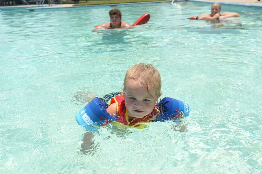 Lifeguards Aaron Aery and Shelbby Short float nearby as Taren Ply, 3, plays enjoys a first swim of the summer at the Vidor City Pool Thursday. Photo taken Thursday, July 16, 2020 Kim Brent/The Enterprise Photo: Kim Brent/The Enterprise