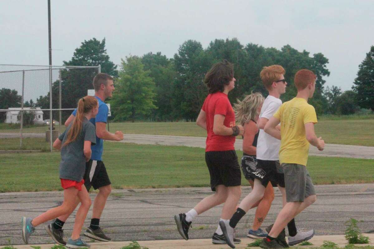 Morley Stanwood coach Shelli McNeil (third from right) and her cross country runners start a workout at the school on Wednesday. (Pioneer photo/John Raffel)