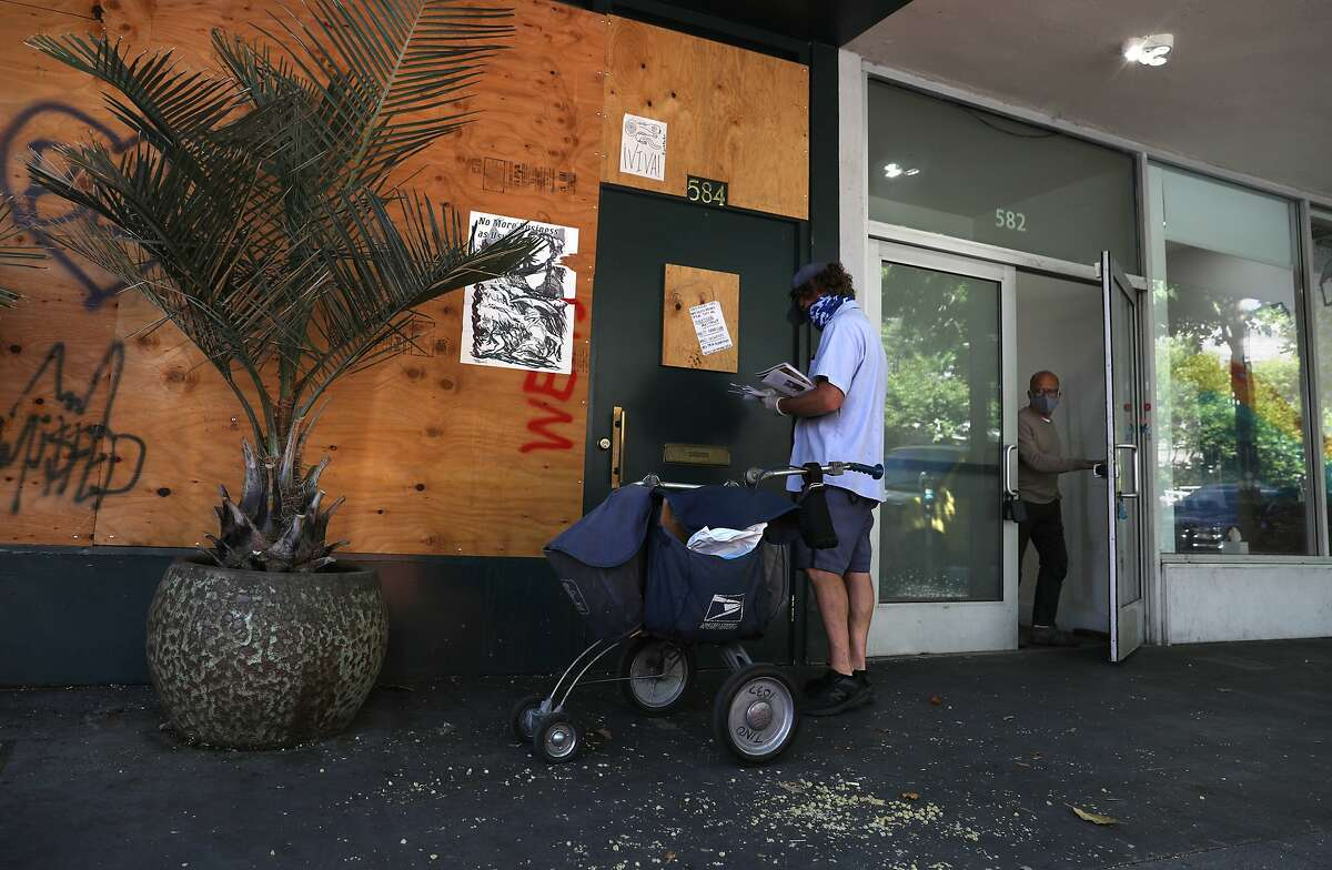 Mail is delivered to a boarded San Francisco restaurant that has been closed since March.
