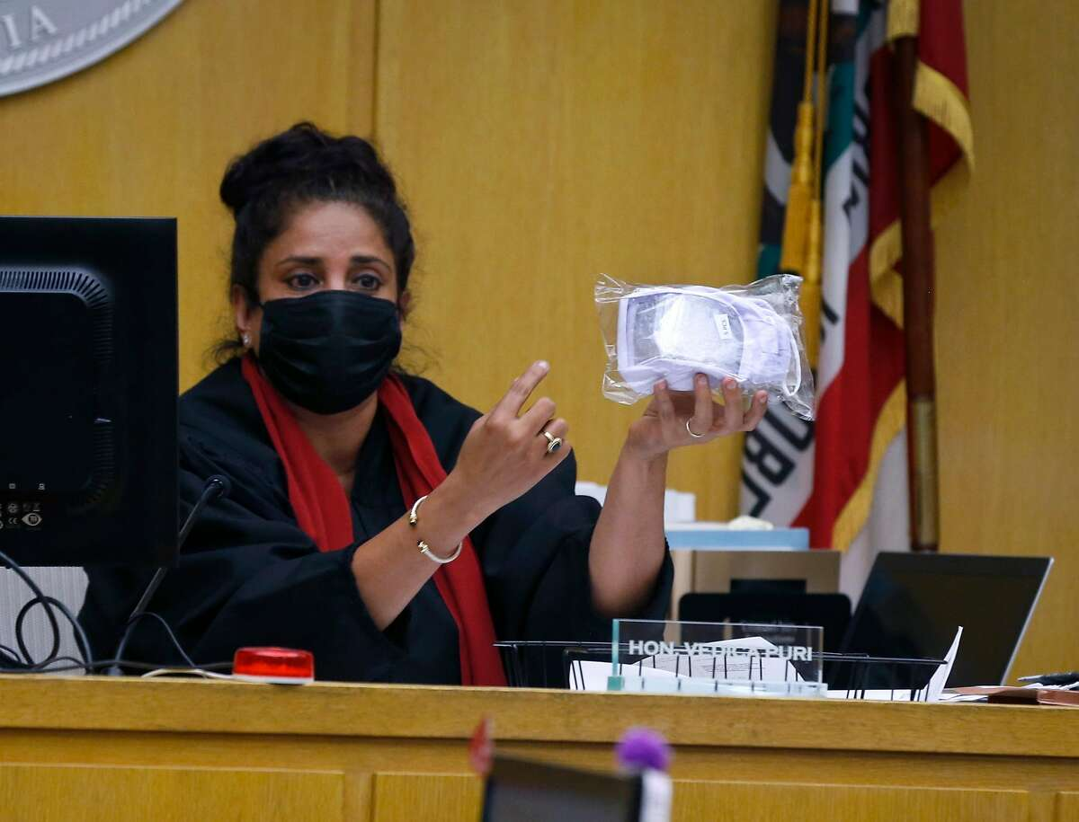 Judge Vedica Puri displays a package of clear face masks that would be made available for witnesses, at a preliminary hearing in the Hall of Justice in San Francisco, Calif. on Thursday, July 16, 2020, before a burglary trial convenes next week. Jury selection will begin next week for the first criminal case to be tried with a jury present during coronavirus pandemic.