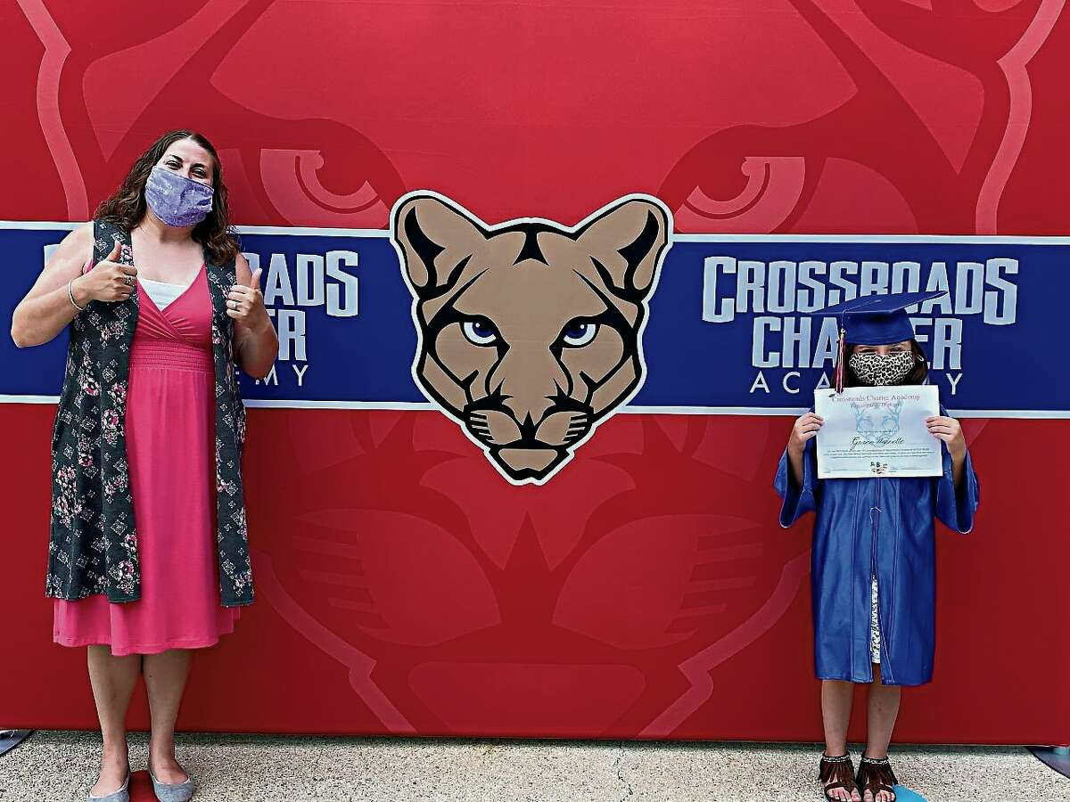 Crossroads Charter Academy teacher Erica Sinicropi and kindergarten graduate Grace Werenette pose six feet apart for a picture after the school's kindergarten commencement ceremony on Thursday. Werenette will be entering first grade in the fall.