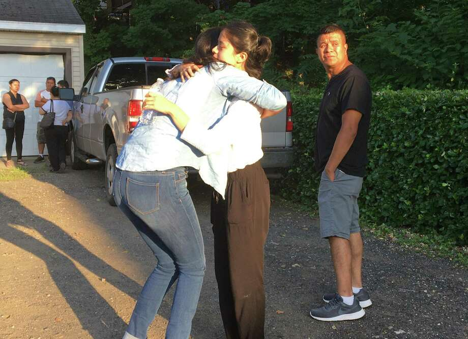 Yaneth Aleman, center, younger sister of the late Lizzbeth Aleman-Popoco, is consoled by a friend as Aleman's father, Albino Aleman, right, looks back on July 16, 2020. The state Office of the Chief Medical Examiner earlier in the day identified remains found a day earlier in a shallow grave behind a Branford restaurant as those of Aleman-Popoco. Photo: Mark Zaretsky / Hearst Connecticut Media