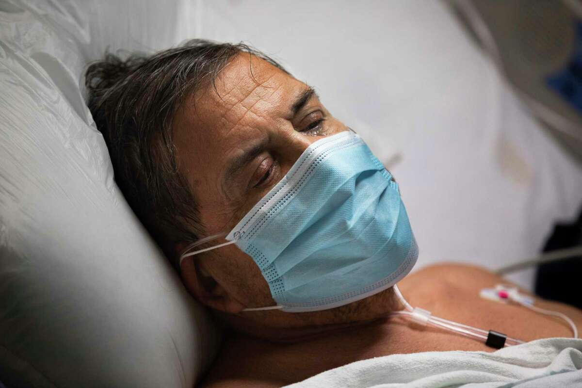 COCID-19 patient Jorge Zambra, 70, gets emotional in his Memorial Hermann-Texas Medical Center bedroom on Thursday, July 2, 2020, in Houston, as he speaks about the care he has received at the hospital. Zambra is being cared for at an intermediate care section of the hospital.