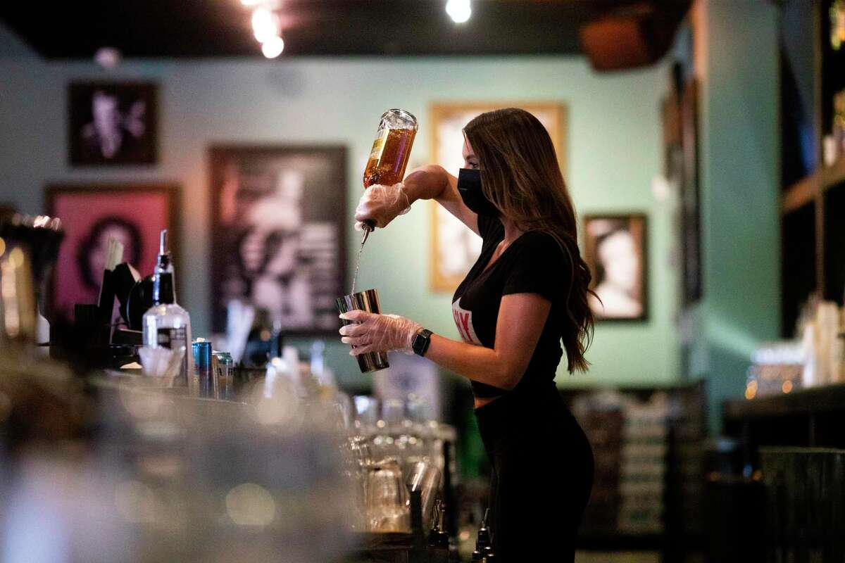A Kirby Ice Houston bartender prepares a drink wearing a protective mask and gloves on the first day of bars being re-open Friday, May 22, 2020, in Houston. Bars were open at the end of May and through much of June.