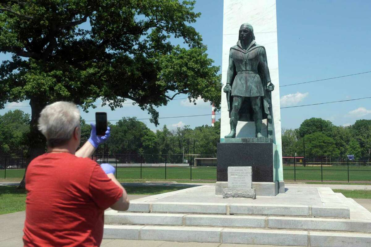 Jesse Angelotti, of Bridgeport, snaps a cell phone photo of the Christopher Columbus statue at Seaside Park, in Bridgeport, Conn. Monday, July 6, 2020. The City of Bridgeport quietly removed the statue from the memorial later Monday afternoon.