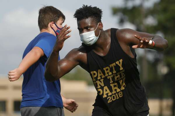 Oak Ridge linebacker KC Ossai, right, wears a face mask as he goes through a drill at Oak Ridge High School?•s strength and conditioning workout, Friday, July 17, 2020.