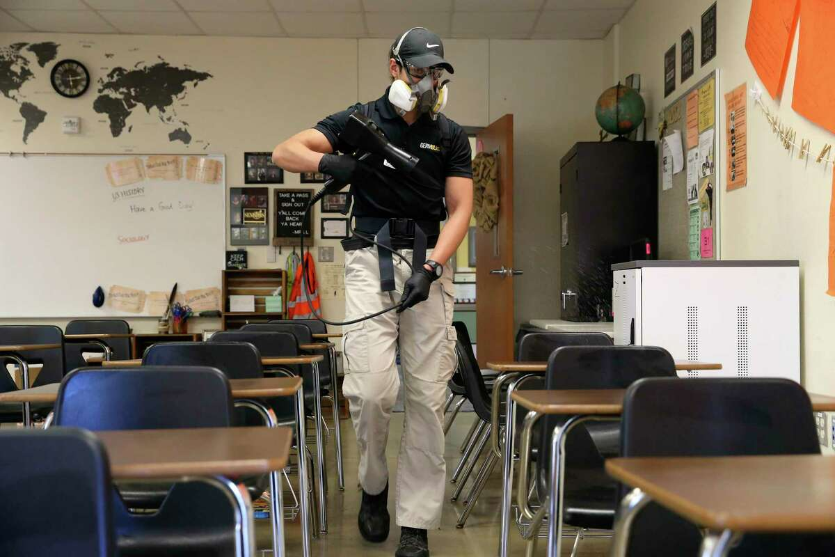 Jonathan Guardiola, with Germblast, sprays an electrostatic charged film of disinfectant on classroom furniture at East Central High School, Wednesday, March 4, 2020. The company was demonstrating how it disinfects various surfaces on school buses, classrooms and locker rooms.