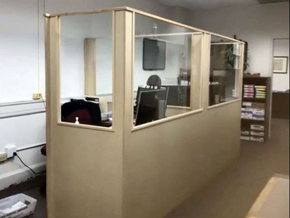 A new composite wood base and glass windows surround a work station in Wilton's tax office as part of recent coronavirus protection renovations.