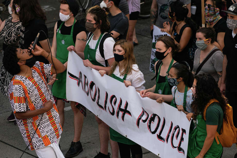 SEATTLE, WA - JULY 16: Protesters march outside a Starbucks location downtown calling for the barista's divestment from the Seattle Police Foundation on July 16, 2020 in Seattle, Washington. The march began at the original Starbucks location in Pike Place Market, stopping at several locations in the city before finishing at the upscale Starbucks Reserve Roastery in the Capitol Hill neighborhood. (Photo by David Ryder/Getty Images) Photo: David Ryder/Getty Images / 2020 Getty Images