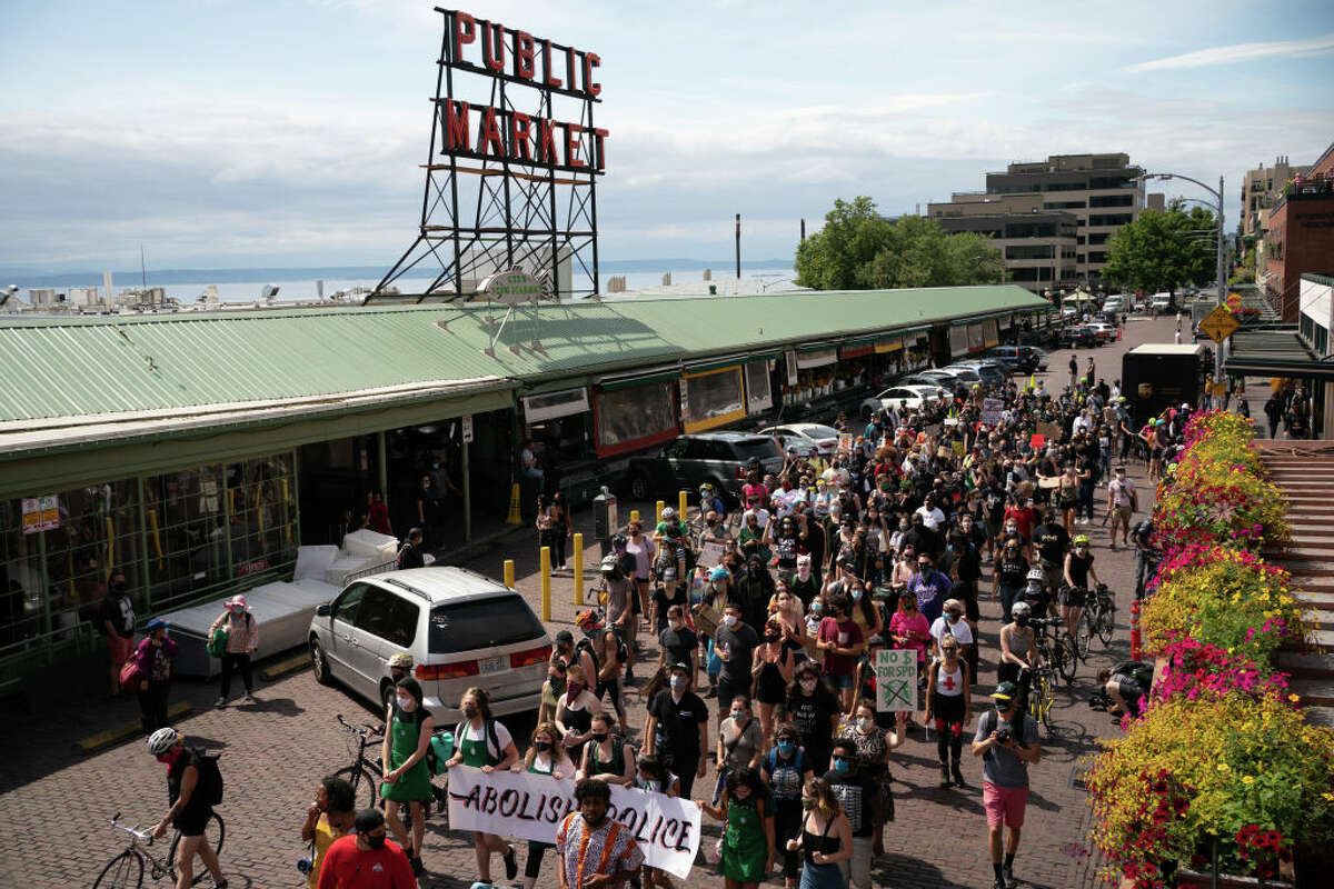 Protesters march through Pike Place Market calling for Starbucks to divest from the Seattle Police Foundation on July 16, 2020 in Seattle, Washington. The march began at the original Starbucks location in Pike Place Market, stopping at several locations in the city before finishing at the upscale Starbucks Reserve Roastery in the Capitol Hill neighborhood.