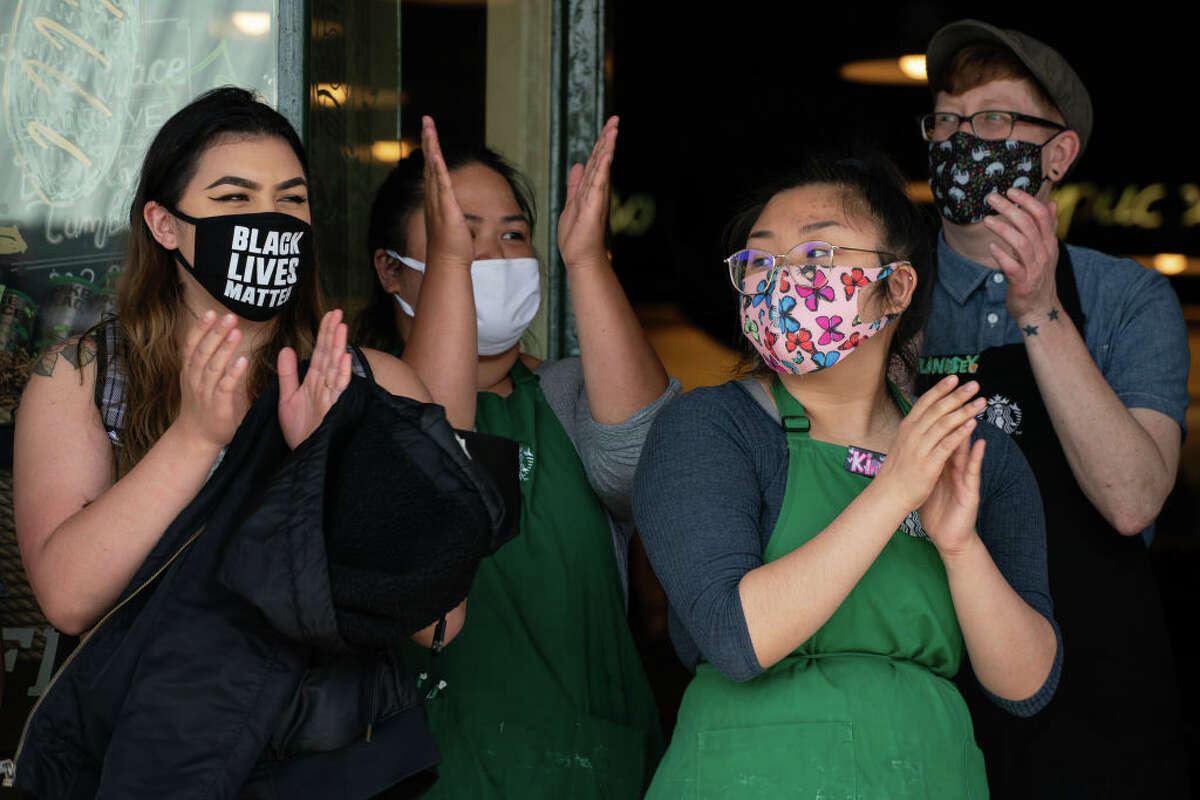 SEATTLE, WA - JULY 16: Starbucks workers and others clap outside the original Starbucks location in Pike Place Market at a rally calling for Starbucks to divest from the Seattle Police Foundation on July 16, 2020 in Seattle, Washington. The march began at the original Starbucks location in Pike Place Market, stopping at several locations in the city before finishing at the upscale Starbucks Reserve Roastery in the Capitol Hill neighborhood. (Photo by David Ryder/Getty Images)