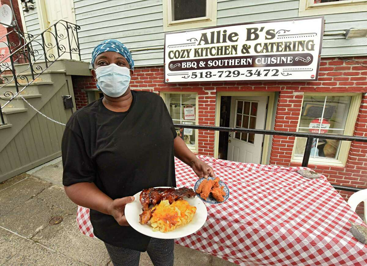 Owner Kizzy Williams holds a plate of her BBQ chicken with mac and cheese and a plate of fried chicken in front of her restaurant Allie B's Cozy Kitchen on Friday, July 17, 2020 in Albany, N.Y. (Lori Van Buren/Times Union7