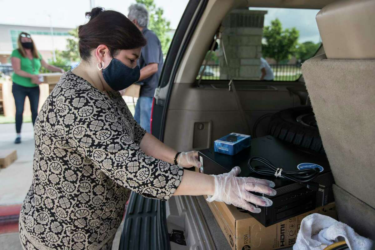 Mary Pizana loads a computer into the back of a vehicle while helping distribute desktop computers to the students at Ridgecrest Elementary School on Friday, May 15, 2020 in Houston. Communities In Schools of Houston distributed 275 computers to help the Ridgecrest students with remote learning amid the coronavirus pandemic and school closings. CIS is teaming up with Comp-U-Dopt to distribute 5,000 computers across the city needed for virtual school work.