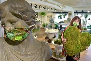 Emily Cross, owner of From Stem to Fern of Clinton, an eclectic gift store that focuses on the sale of botanical art, local artists and artisans, holds a heart fashioned from living moss as a thank you on May 15 to all frontline workers, first responders, healthcare workers and teachers.