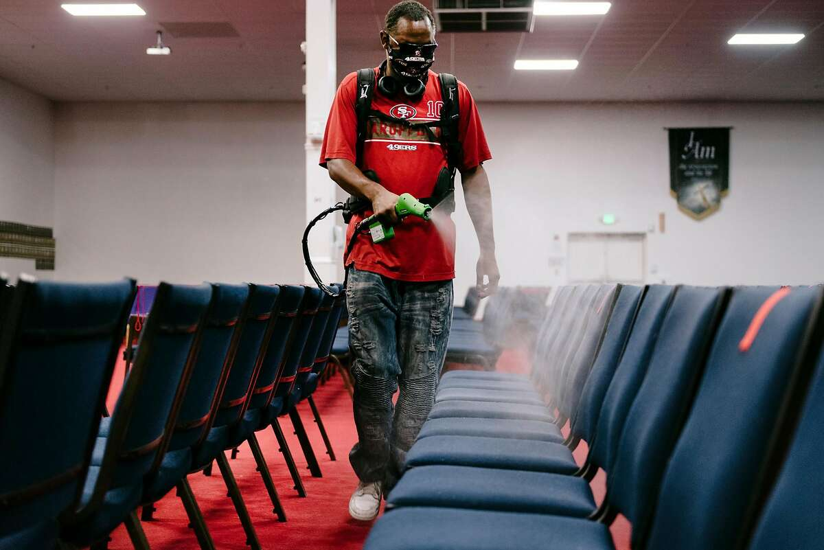 Facilities maintenance technician James Williams demonstrates using an electrostatic sprayer for disinfection seating and interiors at Acts Full Gospel Church of God in Christ in Oakland, Calif, on Thursday, July 16th, 2019.