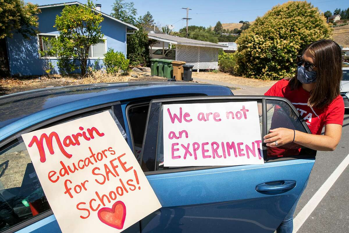 Erin Frazier removes posters on her car after the protest by teachers outside the Marin County Office of Education in San Rafael last week.