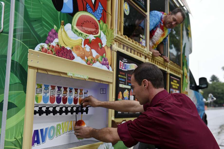 """FILE — A customer pours flavored syrup on a shaved ice as David Schow looks on at the Kona Shaved Ice truck in Denver, Colorado on Aug. 24, 2016. Kona Ice trucks include a """"flavor wave"""" feature, which allows customers to customize their shaved ice dessert. Since the pandemic, Kona Ice of North Marin has discontinued it to prevent the spread of COVID-19. Now, all shaved ice desserts are flavored inside the truck. Photo: Seth McConnell/Denver Post Via Getty Images / Copyright - 2016 The Denver Post, MediaNews Group."""
