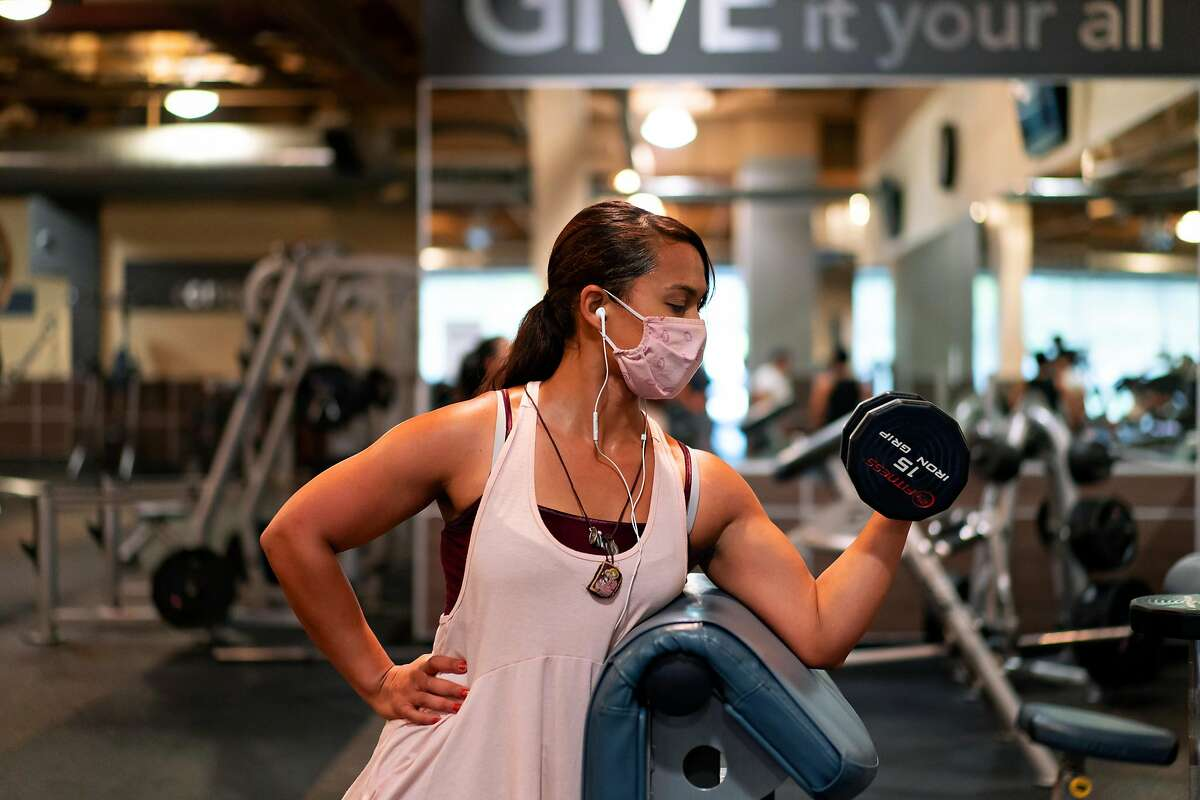 Luisa Norita does some curls in her hour and half session at the 24-hour Fitness in Eastridge Center on Monday, July 13, 2020 in San Jose, Calif.