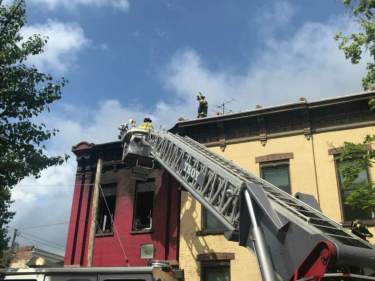 Troy firefighters use an aerial ladder truck to go to the roof of 177 Third St. to check for hotspots after the fire that sent four residents and a firefighter to local hospitals was extinguished Friday July 17, 2020 in Troy, N.Y.