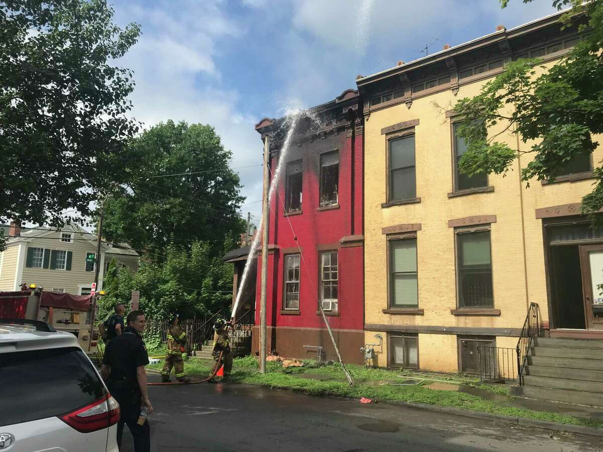 Troy firefighters spray down the exterior of 177 Third St. to prevent the fire from restarting. The fire sent four residents and a firefighter to local hospitals before it was extinguished Friday July 17, 2020 in Troy, N.Y.