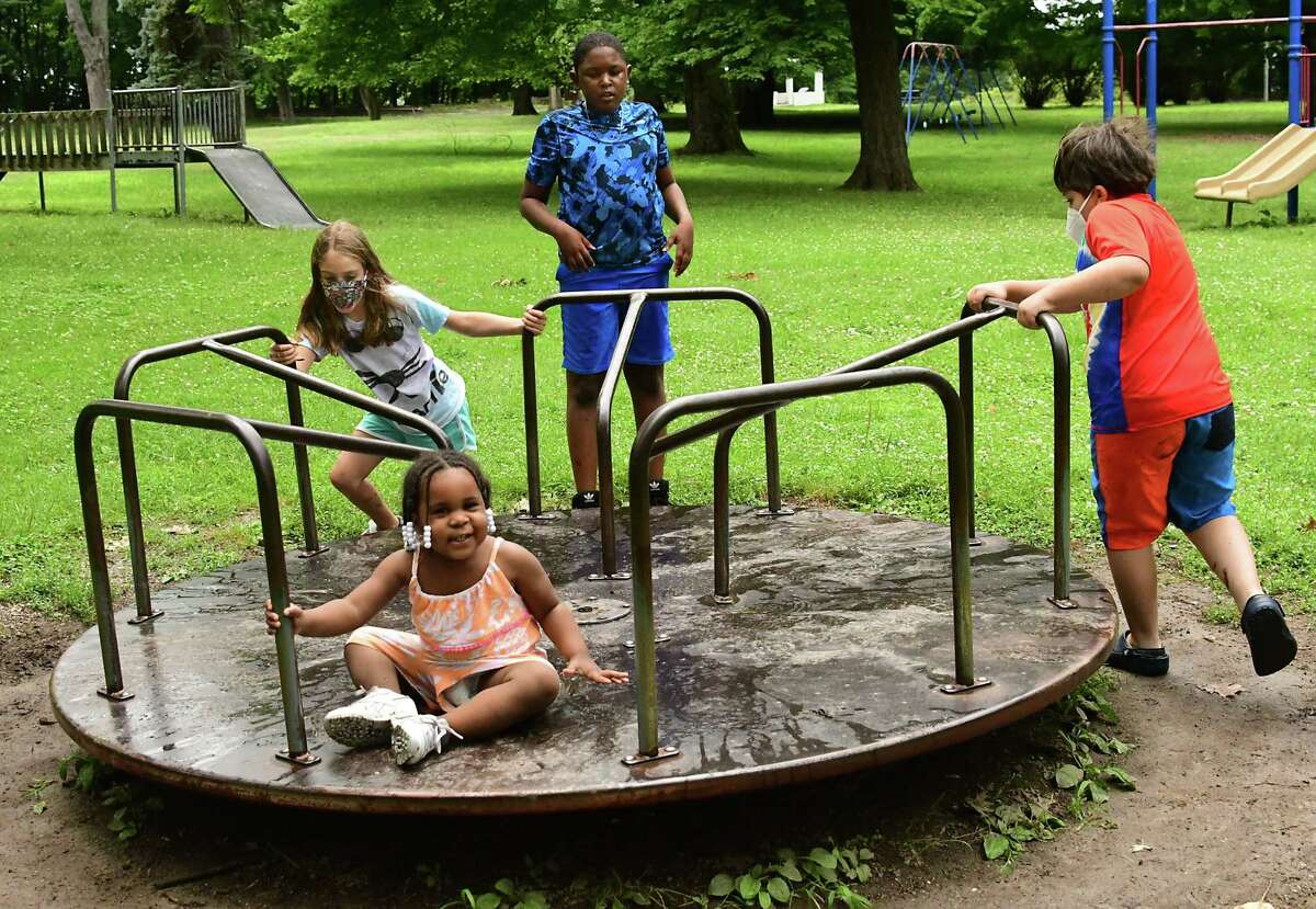 Neve Genovese, 8, of Albany, left, and Zeke Jankowski, 8, of Troy, right, push the merry-go-round where Chy'Nique Scott, 1, of Troy sits and her big brother Sah'Vierre Malloy, 10, keeps and eye on her in Prospect Park on Friday, July 17, 2020 in Troy, N.Y. (Lori Van Buren/Times Union)