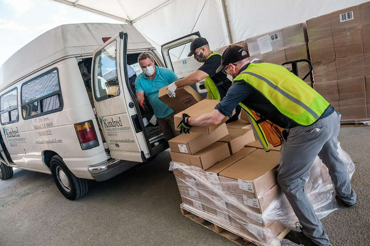 Daniel Flores and Frank Vickers in green vests, help load a vehicle with gowns, masks and other PPE at the Alameda County emergency services warehouse in Dublin on Friday, July 10, 2020.