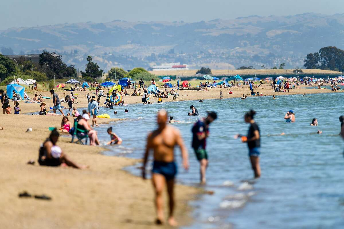 In a photo taken with a telephoto lens, beachgoers gather at Robert W. Crown Memorial Beach on Tuesday, May 26, 2020, in Alameda, Calif. Most people maintained at least fifteen feet between groups.