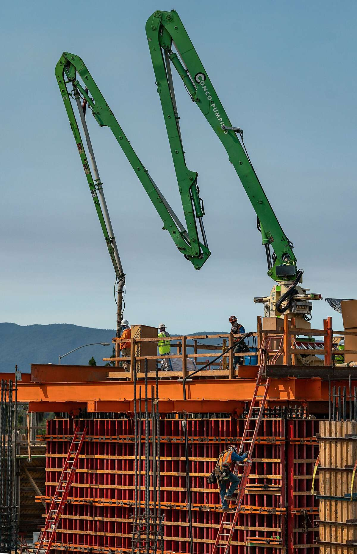 Workers pump wet concrete during the building of the new Adobe tower on Wednesday, July 15, 2020 in San Jose, Calif. The building is part of a big regional plan that predicts heaviest concentration of Bay Area growth in coming decades will be in South Bay, specifically in and around downtown San Jose