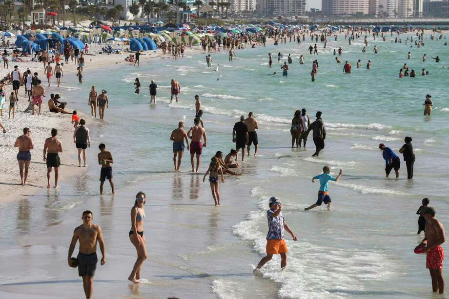 People enjoy Clearwater Beach in Florida on March 18, as the state reopened some say too early. Photo: Eve Edelheit /New York Times / NYTNS