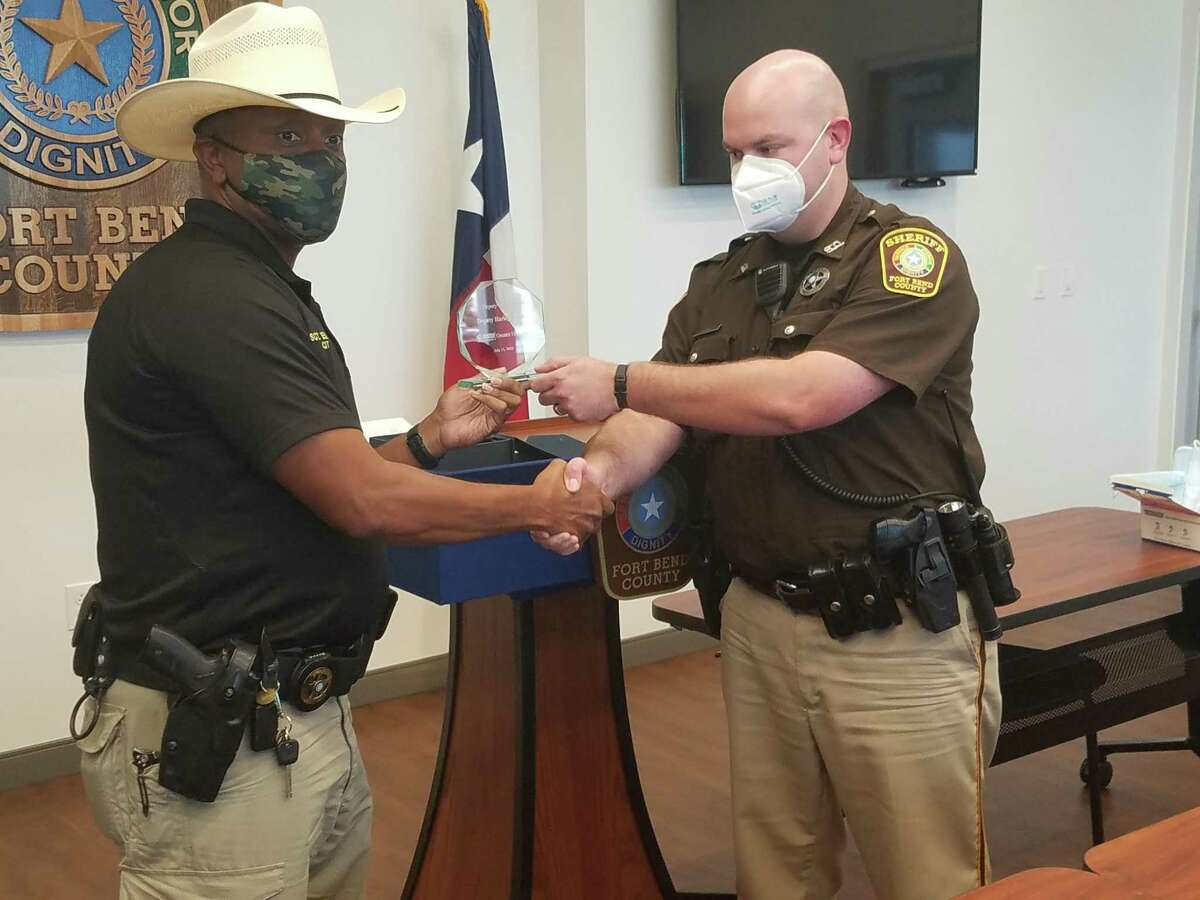 Sgt. Jerome Ellis presents an award to deputy Harley Hayes from the National Alliance for Mental Health on July 17.