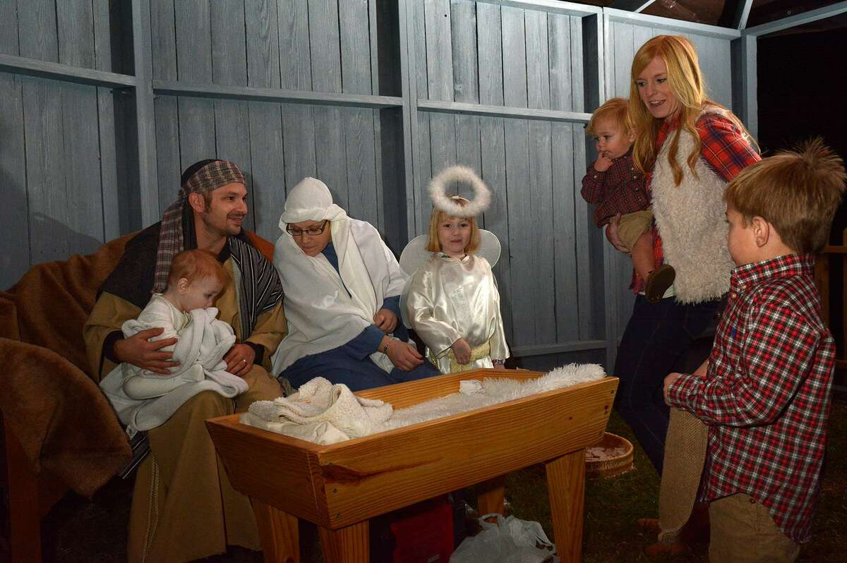 Pastor Brad Otto, from left, playing the part of Joseph, holding his 10 month-old son Logan, playing the baby Jesus, his wife Stacie playing Mary and their daughter London, 5, playing an angel, visit with guests Lea Kellogg and her sons Cannon, 1, and Campbell, 4, during their live recreation of the Christmas manger scene at the Messiah Lutheran Church