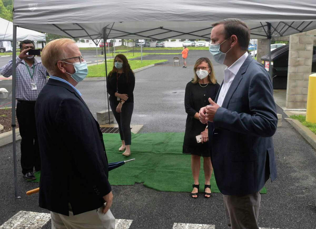 U.S. Sen. Chris Murphy talks with Mayor Mark Boughton as he visits the community health center Connecticut Institute for Communities, to promote increased COVID-19 testing. Friday, July 17, 2020, in Danbury, Conn. Conn State Sen Julie Kushner looks on.