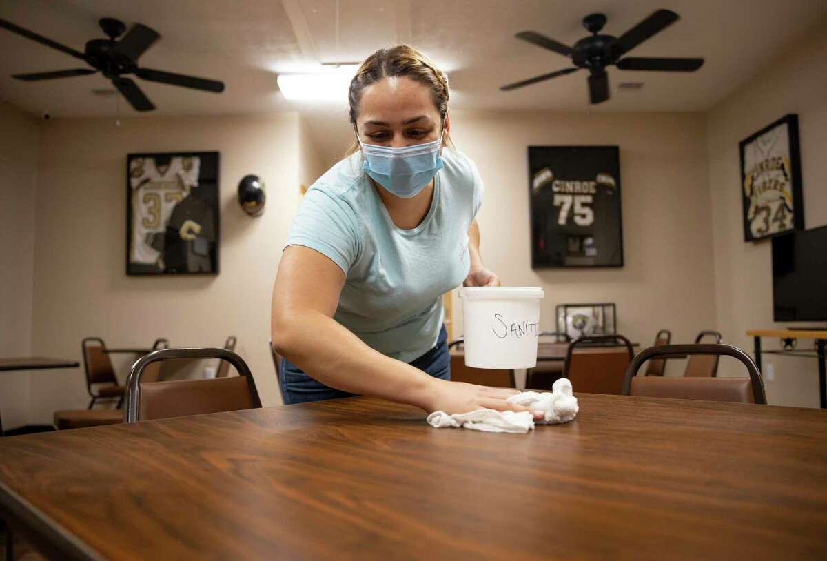 Gaby Pitts, kitchen manager at Darrel's Catering, wipes down and sanitizes a table, Wednesday, July 15, 2020, in Conroe. The restaurant will practice CDC and social distancing guidelines to ensure the safety of it's patrons and staff.