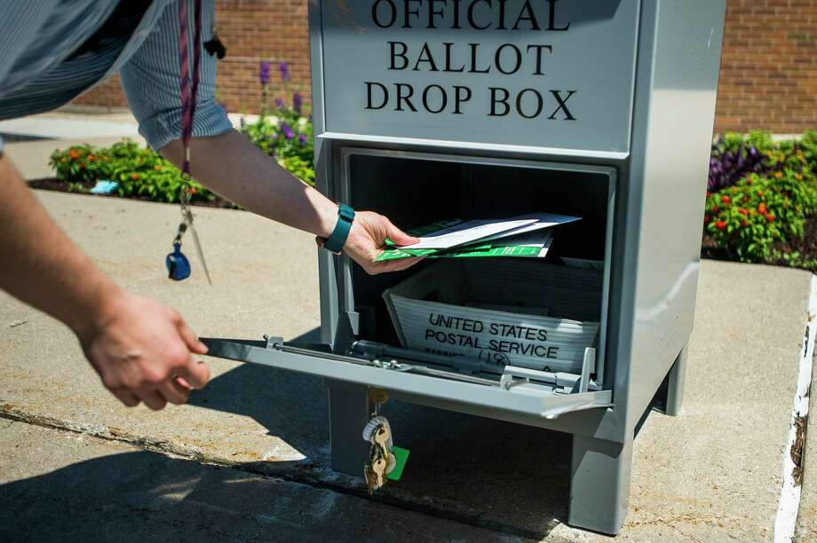Completed absentee ballots for the upcoming primary election are collected from a drop box by a city employee outside of City Hall Friday afternoon. (Katy Kildee/kkildee@mdn.net)