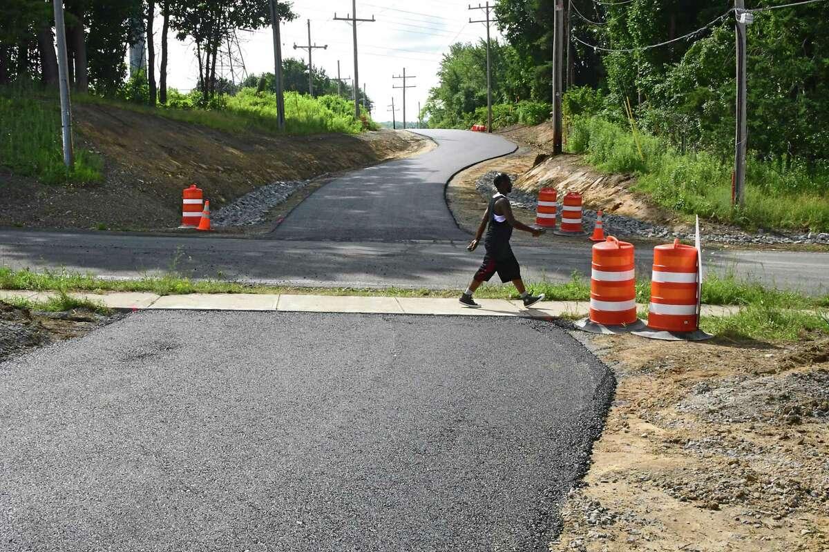 A pedestrian walks down a sidewalk along Forrest Dr. where construction happening for the Electric Trolley trail on Friday July 10, 2020 in East Greenbush, N.Y. (Lori Van Buren/Times Union)