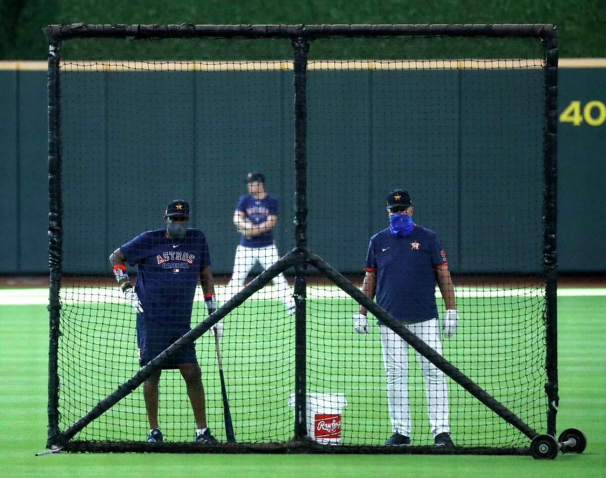 Houston Astros manager Dusty Baker and pitching coach Brent Strom watch batting practice from behind a screen during the Astros summer camp at Minute Maid Park, Friday, July 17, 2020, in Houston.
