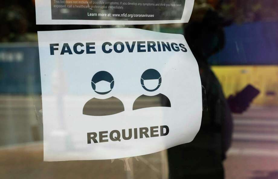 A visitor wearing a mask to protect against the spread of COVID-19 passes a sign requiring masks, Tuesday, July 7, 2020, in Texas. Ahead of the Midland City Council voting this morning on a proposed mask mandate, Councilman Scott Dufford said he would not be supporting the ordinance. Photo: Eric Gay, STF / Associated Press / Copyright 2020 The Associated Press. All rights reserved.