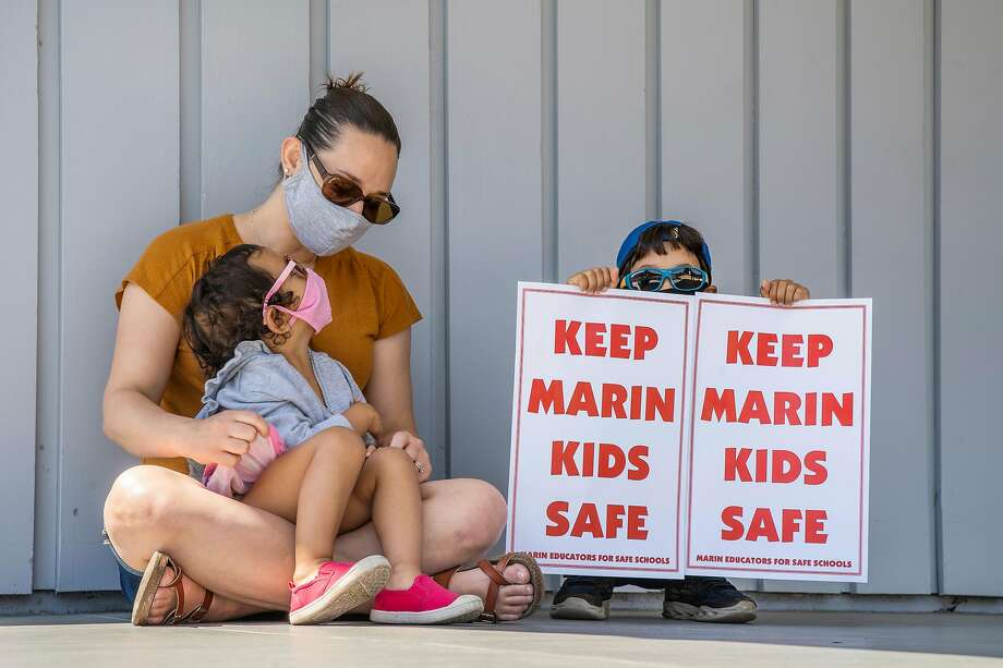 Beverly Chakrabarty with her children Leena, 3, and Kavish, 7, listen during a rally outside the Marin Office of Education to protest the district plans for in-person learning. Photo: Santiago Mejia / The Chronicle