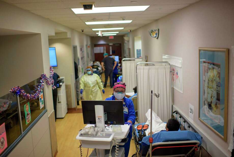 A healthcare worker talks to a patient in the ER at Oakbend Medical Center in Richmond, Texas, on July 15, 2020. - The latest modeling projects the number of COVID-19 deaths in the US to increase further, even as one research team suggests the near-universal use of masks could save 40,000 lives between now and November (Photo by Mark Felix / AFP) (Photo by MARK FELIX/AFP /AFP via Getty Images) Photo: MARK FELIX, Contributor / AFP /AFP Via Getty Images / AFP
