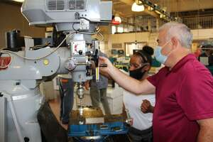 Kesha Redding gets hands-on experience operating a milling machine under the watchful eye of instructor Bob Achille at Eli Whitney Technical High School in Hamden as part of the Skill Up for Manufacturing training program
