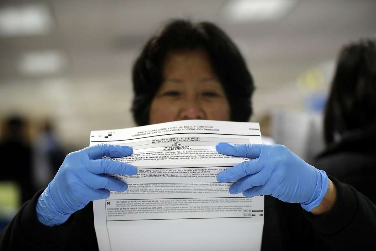 FILE - In this Nov. 4, 2016, file photo, a mail-in ballot is examined at the Santa Clara County Registrar of Voters in San Jose, Calif. The California Assembly on Thursday, June 18, 2020, sent Gov. Gavin Newsom a bill to require county election officials to mail a ballot to every registered voter in the state, which would cement into law the Democratic governor's earlier order to mail out ballots statewide in response to the coronavirus outbreak. Newsom, citing health risks, announced in early May that the state will send every voter a mail-in ballot for the November contest, but that order has been challenged in court. (AP Photo/Marcio Jose Sanchez, File)