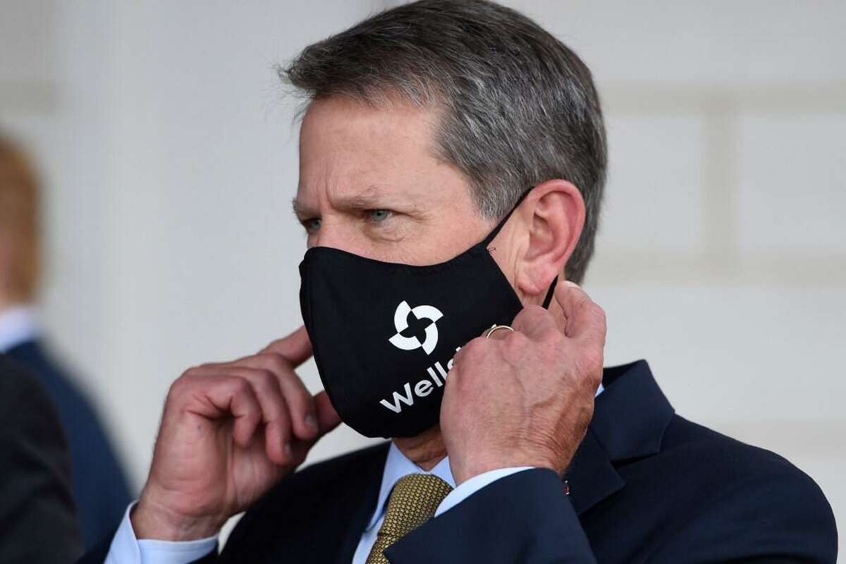 Georgia Gov. Brian Kemp adjusts his mask prior to a bill signing at Wellstar Kennestone Hospital where the hospital opened a new Emergency Room space, Thursday, July 16, 2020, in Marietta, Ga. Mayors in Atlanta and other Georgia cities deepened their defiance of Gov. Kemp on Thursday, saying they want their requirements for people to wear masks in public to remain in place, even after the Republican governor explicitly forbade cities and counties from mandating face coverings.