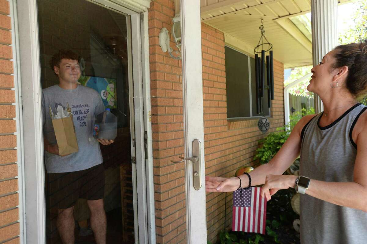 Connie Anselmo, the mother of two Port Neches - Groves alumni, drops off a weekly treat, this time sweet tea and jerky - to graduating senior Jake Plante at his house Thursday, April 23. She has been making weekly stops since joining in the Adopt-A-Senior program, and plans to continue bringing him small treats up through graduation. Nederland and Port Neches - Groves both have been creating opportunities for community members to make this year's graduates feel special in a time of upheaval. Photo taken Thursday, April 23, 2020 Kim Brent/The Enterprise