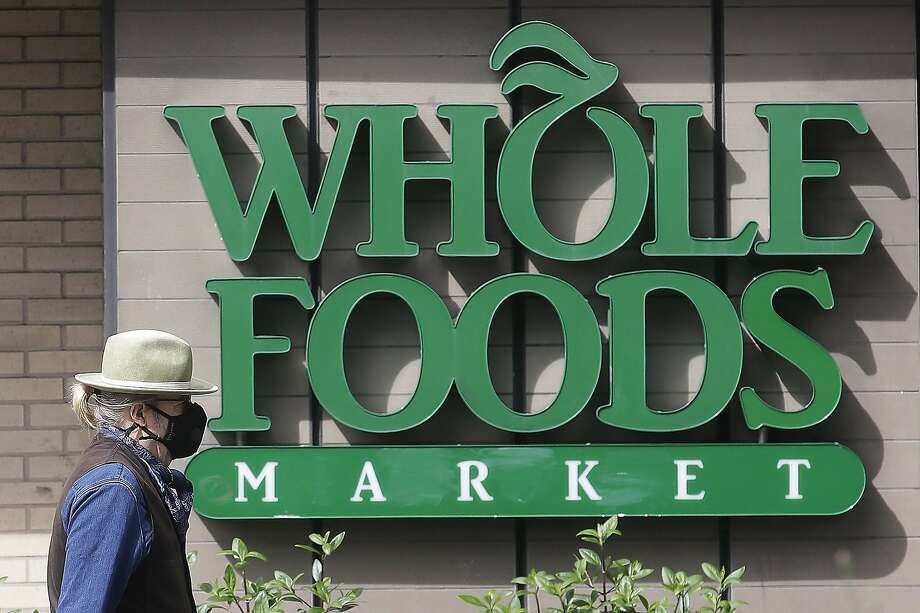 "A pedestrian wears a mask while walking past a sign for a Whole Foods Market in San Francisco, Tuesday, March 31, 2020. A protest is being staged at a Berkeley Whold Foods location Friday, after an employee said that managers would not allow her to wear a mask that read ""Black Lives Matter"" on it. Photo: Jeff Chiu / AP Photo"