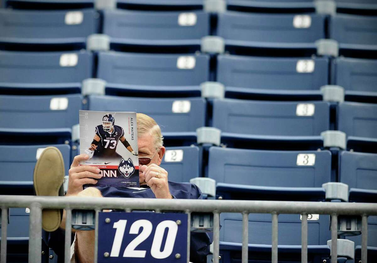A fan reads a program before an NCAA college football game between Connecticut and Boise State at Rentschler Field, Saturday, Sept. 13, 2014, in East Hartford, Conn. (AP Photo/Jessica Hill)