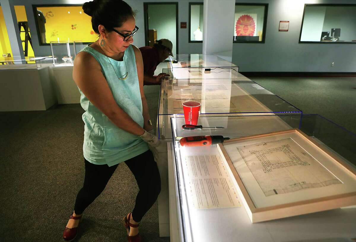 Dr. Sarah Zenaida Gould, left, Lead Curatorial Researcher with Institute of Texan Cultures, and Domingo Yruegas set up the exhibit Nuestra Historia-Our History: Spain in Bexar County, with Spanish colonial documents from Spain, on Monday, April 25, 2016.
